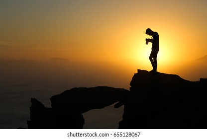Silhouette of Boy looking down at camera after taking sunset landscape shot