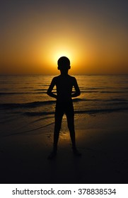 silhouette of a boy on the beach in front of the setting sun