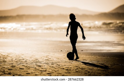 Silhouette of boy on the beach, playing football