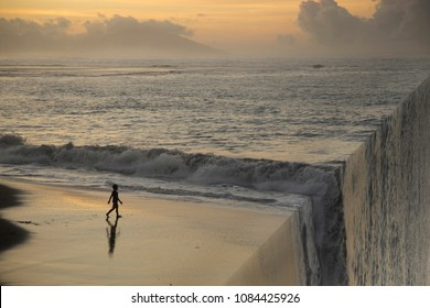 Silhouette of a boy on the beach at sunset. Bending inception effect