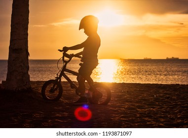 silhouette of boy on bicycle with helmet in the sunset