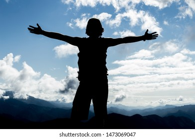 silhouette of a boy with open arms on top of a mountain in Spain called pedraforca