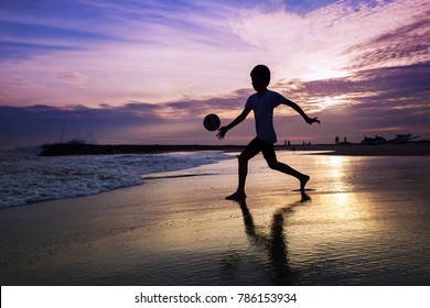 Silhouette of boy playing football on beach during sunset