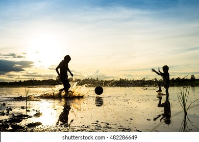 Silhouette of boy playing football in water at countryside in thailand