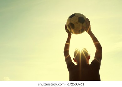 Silhouette of the boy playing with a soccerball against the background of the sky, the rear view, toned