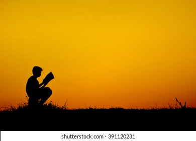 Silhouette a boy reading book  at sky sunset . warm tone and soft focus