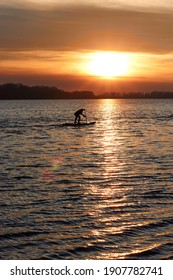 Silhouette of a boy rowing on a SUP (on stand up paddleboard) at sunset in a winter river
