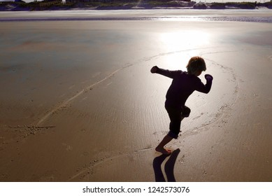 Silhouette of boy running on the beach at sunset