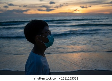 Silhouette A boy with surgical mask on the beach and sunset time
