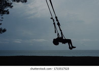 Silhouette of a boy swinging on a swing, against the background of the sea