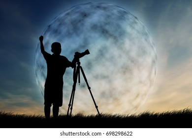Silhouette of boy using camera shooting moon