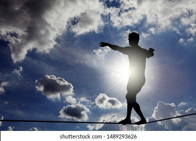 Silhouette of a boy walking on a tightrope against a surreal blue cloudy sky.