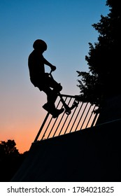 The silhouette of a boy who drives up a half pipe with his stunt scooter and does a tailwip