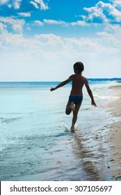 Silhouette of a boy who runs along the seashore