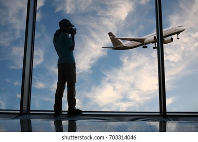 Silhouette of a boy who takes a photograph of a take-off plane