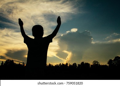 Silhouette of a boy worshipping with his hands lifted up expressing his praise, happiness and freedom in the nature with sunset and sky in the background.