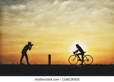 Silhouette of boyfriend taking pictures of girlfriend cyclists. couple are cycling happily in time for sunset.