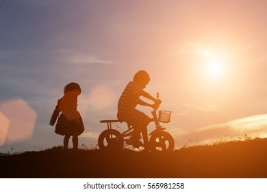 Silhouette of boys and girls are happily rides at the evening sunlight.