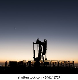 Silhouette of BPU crude oil pump in the oilfield at sunset golden hour