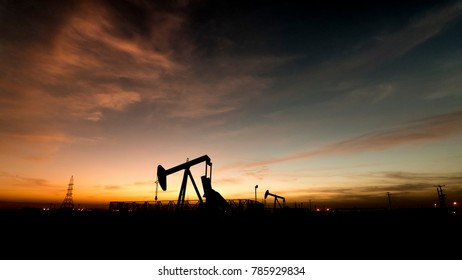 Silhouette of BPU crude oil pump in oilfield at sunset golden hour