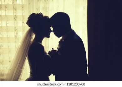 Silhouette of bride beautiful young woman and groom handsome african American man share love head to head on background of window