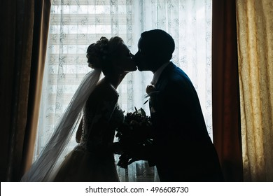 Silhouette of bride beautiful young woman and groom handsome african American man with wedding bouquet kiss on background of window