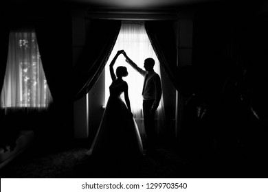 Silhouette of bride and groom by the window. Bride and groom dancing. Newly married couple. Wedding day. The groom holds the bride's hand. The couple dancing the waltz. Wedding dance rehearsal