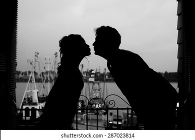 silhouette of bride and groom kissing