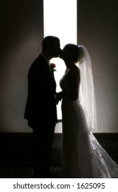 A silhouette of a bride and groom kissing in front of a narrow window.