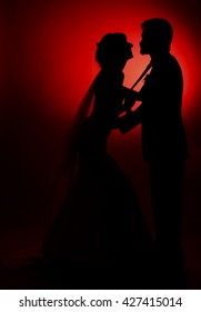 The silhouette of the bride and groom on a red background
