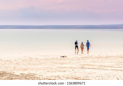 Silhouette of bride and groom and their photographer walking on Salt Lake (Tuz Golu) to take wedding photo in Turkey