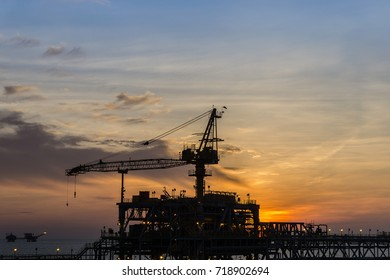 Silhouette of bridge connected production platform complex at oilfield during sunset