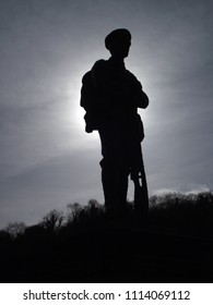 Silhouette of a bronze life sized figure of a WW1 soldier in full marching order resting against his gun as the sun goes down behind the statue casting a soft halo effect backdropped by an evening sky