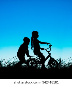 silhouette of a brother and sister, cycling at sunset