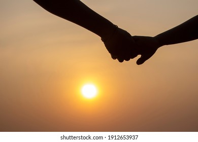 silhouette Brother and younger brother holding hands on the beach with evening sunset background