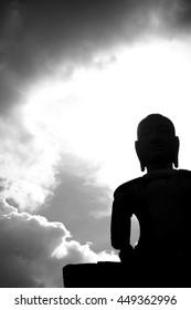 Silhouette Buddha statue in black and white shot.