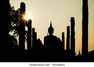Silhouette of a buddha statue and temple