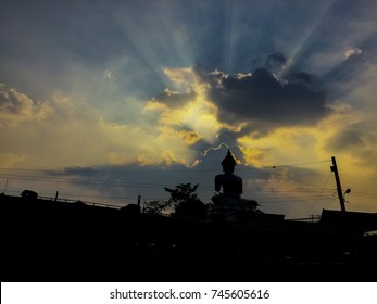Silhouette of Buddha statue in Thailand at twilight time with golden sky