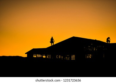 Silhouette of builders working on new construction home during sunset