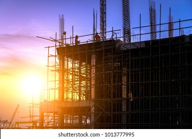 Silhouette of building construction site on heavy industry and background sunset pastel