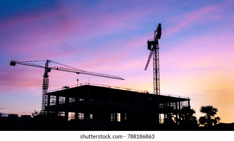 Silhouette of building with crane at sunset