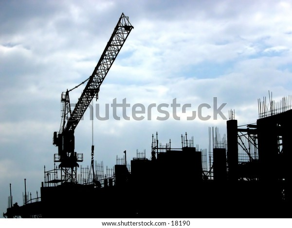 Silhouette of a building site on a cloudy day.