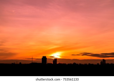 Silhouette of the buildings at the metropolis or city in the morning with beautiful sky colorful, cloudy and sunrise background