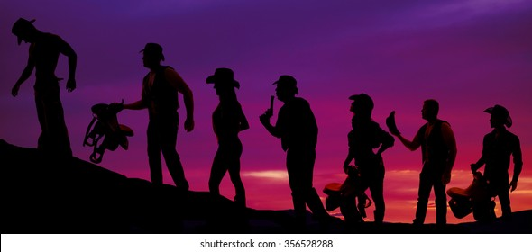 a silhouette of a bunch of cowgirls and cowboys, with saddles walking up a hill.