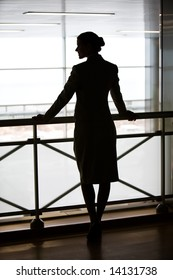 Silhouette of business ladyâ??s back standing on the balcony and touching its railing