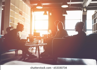 Silhouette of business group brainstorming new plan. Team meeting on the couch. Big open space office. Five people. Intentional sun glare