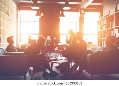 Silhouette of business group discussing new plan. Team meeting on the couch. Big open space office. Five people. Intentional sun glare