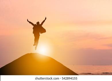 Silhouette of Business man Celebration Success Happiness on a mountain top Sunset Evening Sky Background, Sport and active life Concept.
