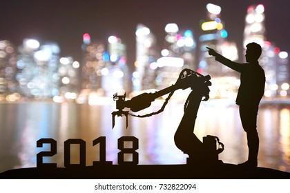 Silhouette of business man command automation robot advisor for 2018 new year technology , industry 4.0 , artificial intelligence  trend concept. Blur Bokeh flare light night building background.