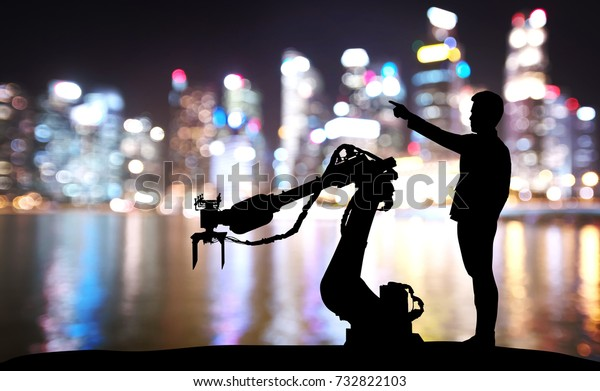 Silhouette of business man command automation robot arm machine technology , industry 4.0 , artificial intelligence  trend concept. Blur Bokeh flare light night building background.
